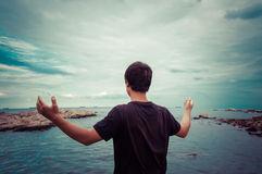 asian-boy-joyful-ocean-hands-up-64183560